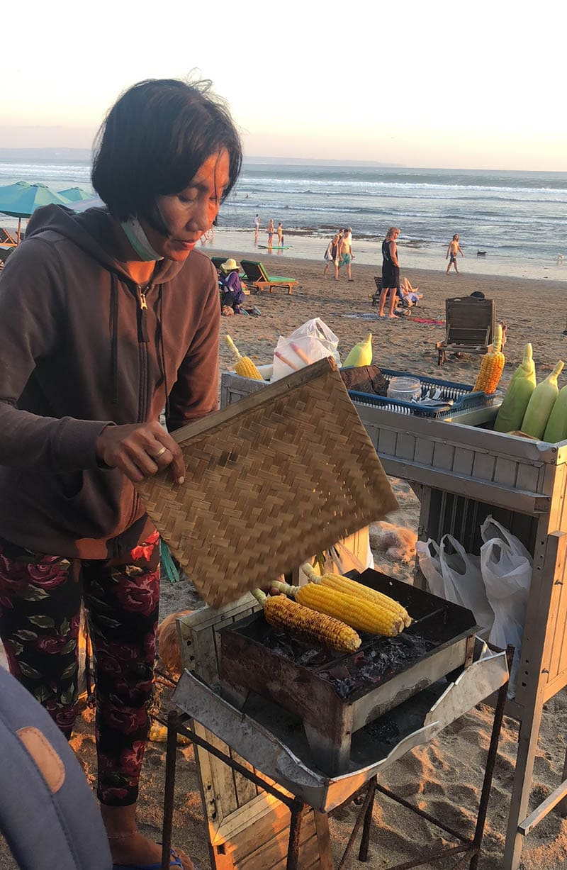 Local Lady Selling Corn on the cob at the beach Travel Guide to Bali